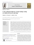 Cyclic settlement behavior of strip footings resting on reinforced layered sand slope